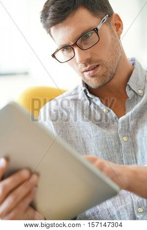 Portrait of man with eyeglasses websurfing on digital tablet