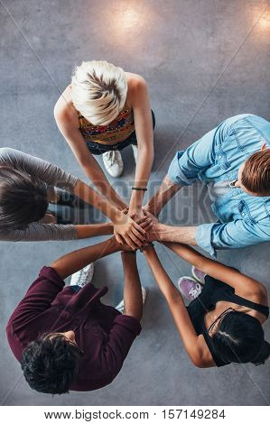 Top view shot of young college students putting their hands on top of each other symbolizing unity and teamwork.