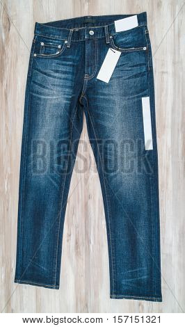 Blue jeans with price tag on  wooden background