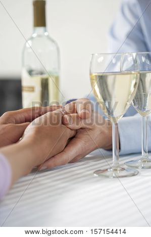 Female holding her hand over male hand at Valentine s day with a bottle white wine and glasses. Close-up