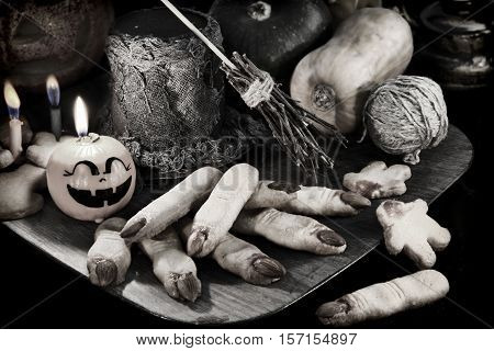 Scary black and white still life with finger cookies, pumpkin candles and magic Halloween objects, vintage concept
