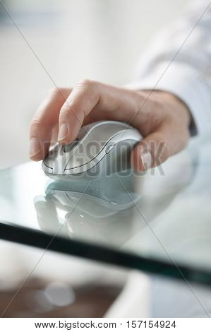 Young man's hand clicking on a cordless computer mouse on a green glass table