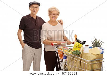 Seniors with a shopping cart full of groceries isolated on white background