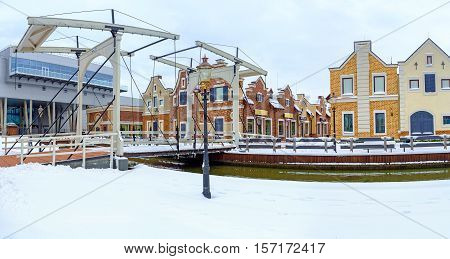 KIEV UKRAINE - NOVEMBER 11 2016: The snowy embankment of the canal in Dutch Revival style shopping city with the drawbridge leading to fashion boutiques and cafes on November 11 in Kiev.
