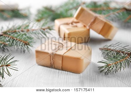 Pieces of coniferous soap and branches on wooden background, close up view