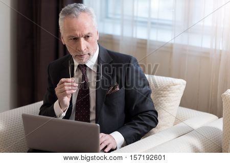 I have an idea. Involved serious bearded businessman holding glasses and sitting in the hotel while working with the laptop