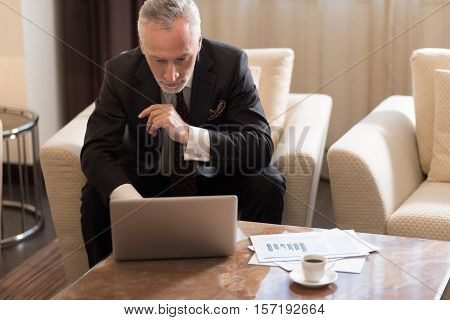 Searching the solution. Involved pleasant bearded businessman sitting in the hotel while working with the laptop and being concentrated