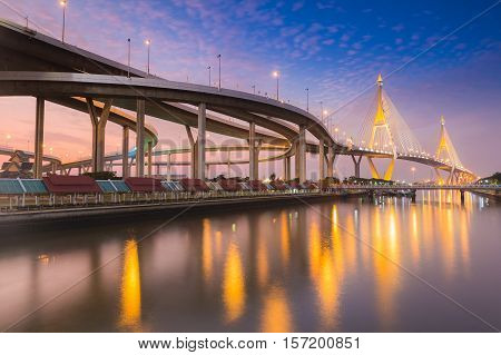 Twin suspension bridge connect to highway interchanged river front night view