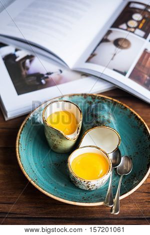 Homemade lemon curd or cream in a bowl on a plate on a wooden rustic kitchen table, selective focus