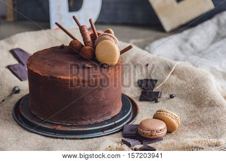 Chocolate cake covered with cocoa powder, macaroons and chocolate pieces lying around on the sackcloth