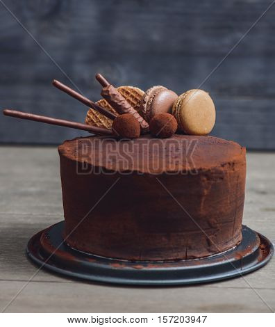 Chocolate cake decorated with coffee and caramel macaroons, waffles, truffles  and chocolate sticks