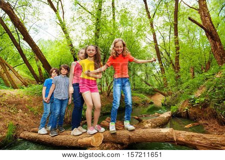 Five happy friends, teenage girls and boys, crossing through a log over the river one by one in summer forest