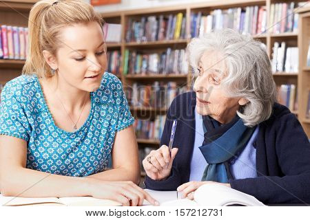 Senior Woman Working With Teacher In Library