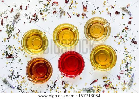 Diagonally in 2 rows 6 cups with different types of tea black green hibiscus chamomile peppermint lavender on white background of scattered tea leafs. Six types of tea on a white diagonal lines.