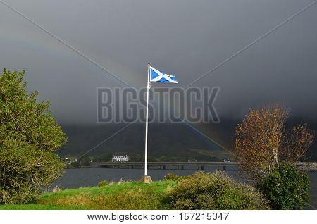 Rainbow across the sky with the Scottish flag at Eilean Donan Castle.