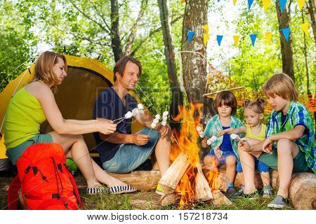 Big happy family, young parents and three kids, roasting marshmallows on the sticks over the fire at campsite in summer