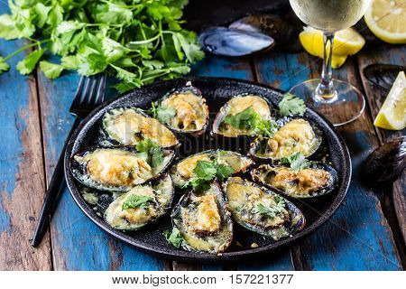 Seafood. Shellfish mussels. Baked mussels with cheese, cilantro and lemon in shells on cast iron black plate. Plate of mussels, cold white wine, lemon and cilantro on old wooden blue background.