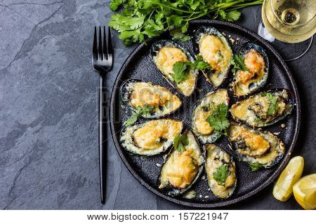 Seafood. Shellfish mussels. Baked mussels with cheese, cilantro and lemon in shells on cast iron black plate. Plate of mussels, cold white wine, lemon and cilantro on black stone background. Top view