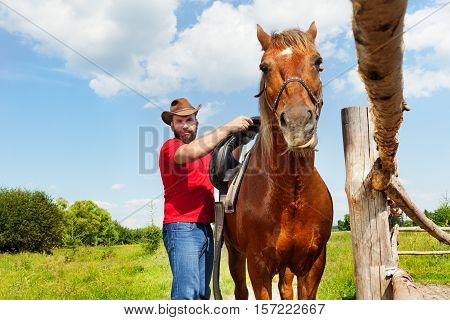 Cowboy saddling his chestnut brown horse at the farm in summer