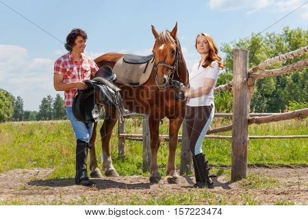 Portrait of young man and woman saddling beautiful bay horse at sunny day in summer