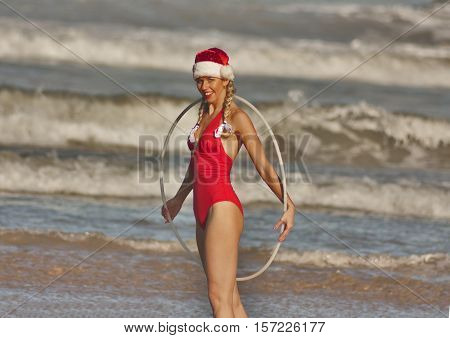 Girl in red bikini and Christmas hat with hula hoop on the beach
