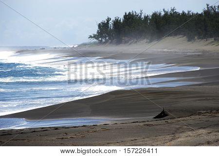 Very dark black sand on the beach on the island Reunion France The sand is vulcanic origin