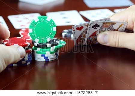 colorful chips on a wooden table in a game of Texas Hold'em Poker