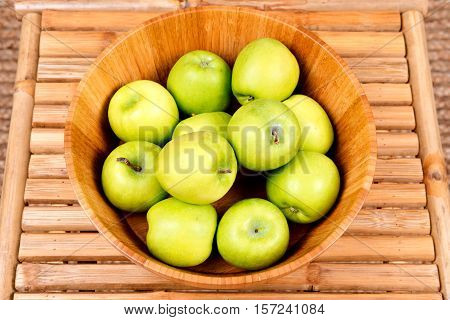 Organic granny smith apples in wooden bowl on bamboo table