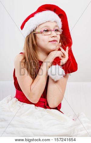 Christmas holiday concept. Toddler girl wearing Santa Claus hat and christmassy dress.