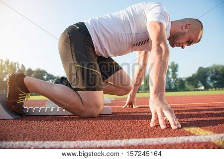 Male athlete on starting position at athletics running track. Runner practicing his sprint start in athletics stadium racetrack.
