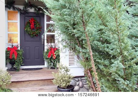 Front door with a Christmas wreath and bows. Also available in vertical.