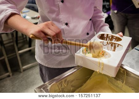 Mid section of worker filling chocolate mould in kitchen