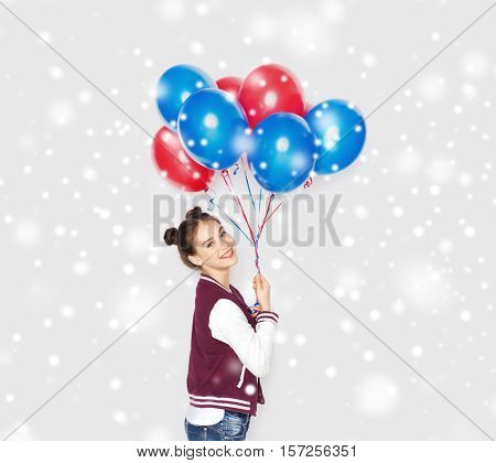 winter, christmas, people, holidays and party concept - happy smiling pretty teenage girl with helium balloons over gray background and snow