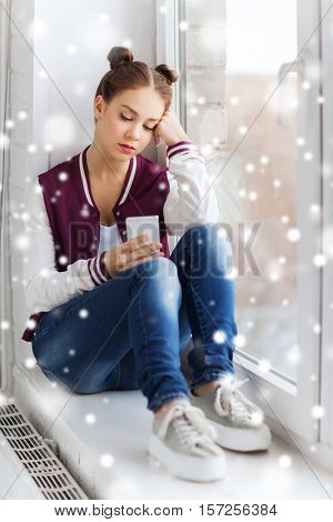 people, winter, christmas, technology and teens concept - sad unhappy pretty teenage girl sitting on windowsill with smartphone and texting over snow