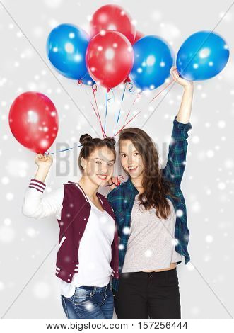 winter, christmas, people, holidays and party concept - happy smiling pretty teenage girls or friends with helium balloons over gray background and snow
