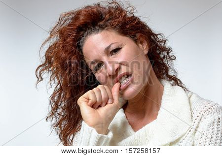 Thoughtful Young Woman Chewing Her Thumb Nail