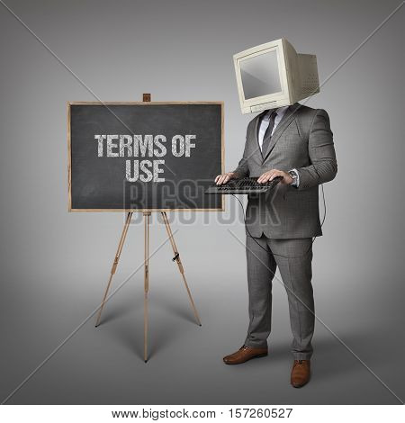 Terms of Use text on blackboard and computer monitor on businessman head