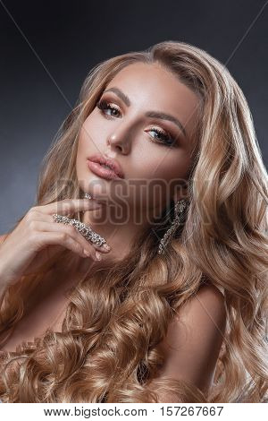 Beauty woman face with beautiful make-up colors. Blond hair wavy hair jewelry clear skin beautiful face. Portrait shot in studio on a gray background.