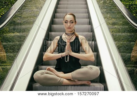 Beautiful Young Woman Meditating on the Escalator with Forest Background Sitting in Yoga Lotus Posture with Closed Eyes. Stress Free Concept.