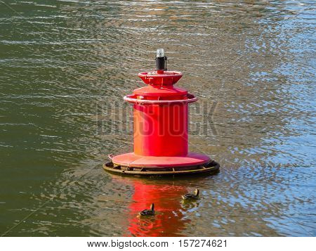 Red river buoy on a water with reflections