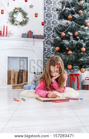 Writing letter to santa. Beautiful girl makes wish list of presents for christmas in decorated room. Waiting for gift. Prepare for winter holidays, vertical image