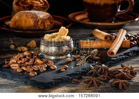 Brown sugar, coffee grains and sticks of cinnamon on a black plate from slate in style a rustic