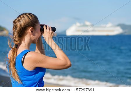 Young female tourist looking through binoculars at white cruise ship (liner) and enjoying scenic sea view. Woman wearing blue dress. Her hair braided in French plait. Outdoor portrait in summer.