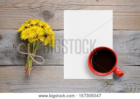 Dandelion flowers blank paper and coffee cup on wooden background