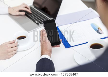 Close up of a bespectacled businessman looking at his smartphone screen and drinking coffee from a white cup. His coworker is typing