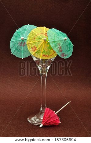 A martini glass displayed with cocktail umbrellas