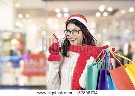 Christmas Shopping. Happy Girl With Credit Card In Shopping Mall. Shopping Bags. Shopping Center. Christmas Sales