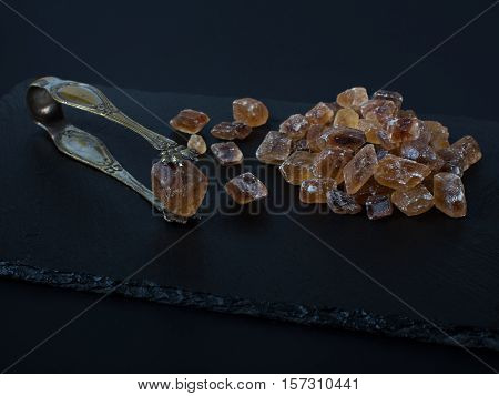 Brown sugar on black background cubes with nippers