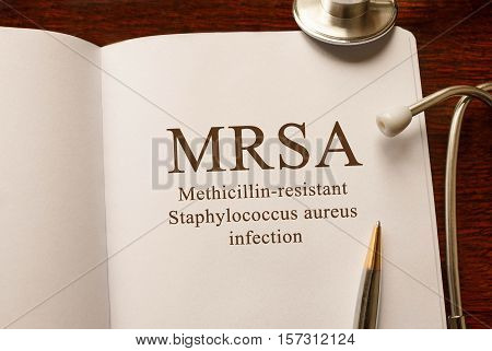 Page with MRSA Methicillin-resistant Staphylococcus aureus infection on the table with stethoscope medical concept