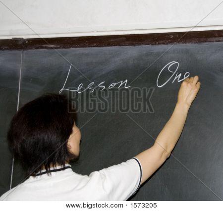 Female Teacher Writing On A Blackboard
